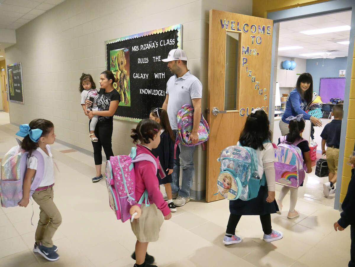 Parents look on as students walk into their classroom for the first day of the 2019-2020 school year at Octavio Salinas Elementary, Wednesday, August 14, 2019.