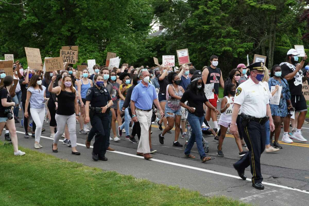 """Demonstrators repeat chants such as """"Black Lives Matter,"""" and """"White Silence is Violence,"""" in New Canaan at a peaceful well-attended march, June 4, 2020, to protest about police violence against black people, in particular George Floyd's death, May 25, 2020."""