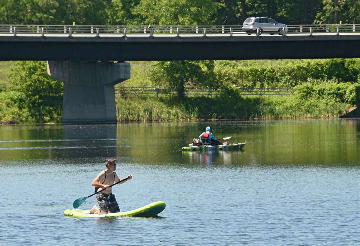 A young man on his paddle board makes his way past a fisherman in his boat at Six Mile Waterworks Park on Tuesday, June 16, 2020 in Albany, N.Y. (Lori Van Buren/Times Union)