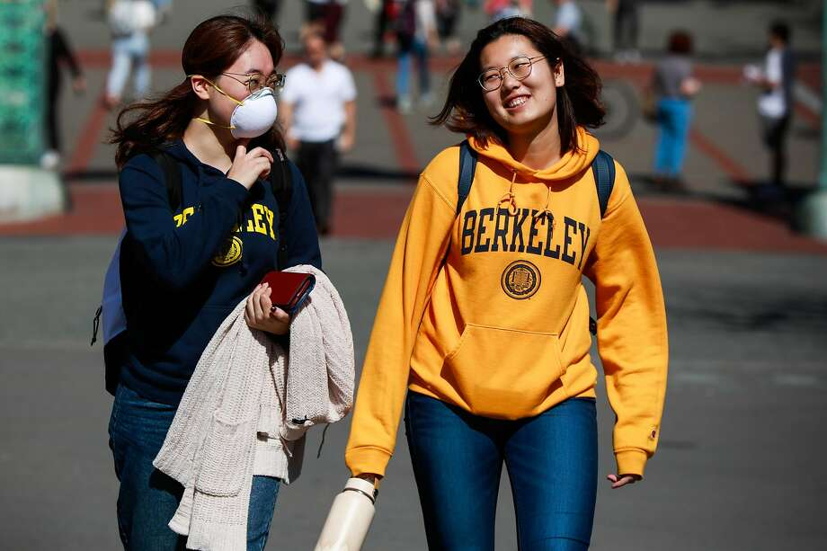 (L-r) Chris Shi, 21 wears a mask while chatting with Monica G. on the UC Berkeley campus on Wednesday, March 4, 2020 in Berkeley, California. A Berkeley resident recently tested positive to the coronavirus. Photo: Gabrielle Lurie / The Chronicle