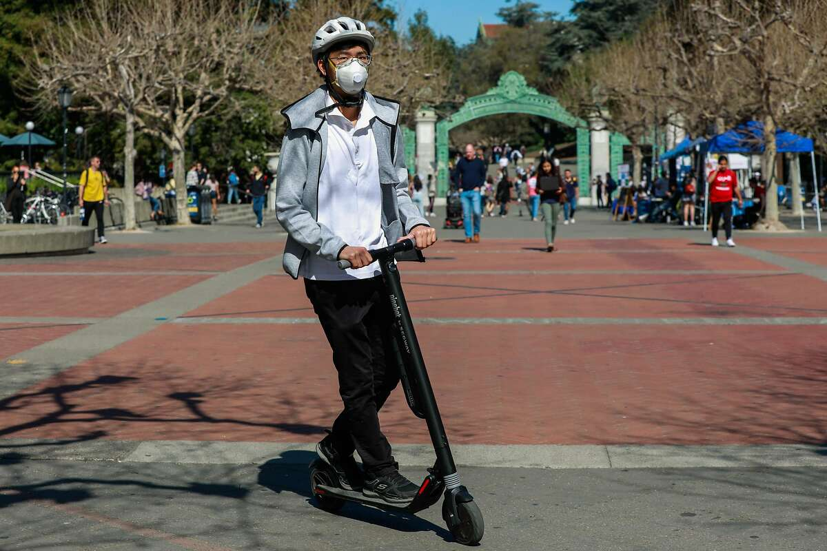 A man wears a mask while scootering on the UC Berkeley campus on Wednesday, March 4, 2020 in Berkeley, California. A Berkeley resident recently tested positive to the coronavirus.