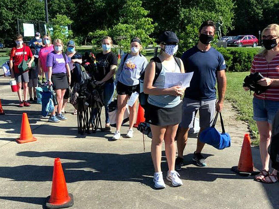 Players, wearing protective face masks, wait in line to register for the Alton Junior Net Tournament at the the Simpson Tennis Complex at Gordon Moore Park