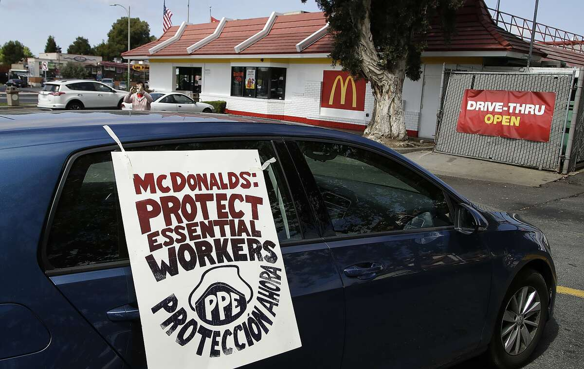 FILE - In this April 21, 2020, file photo, motorists protest what they say is a lack of personal protective equipment for employees as they shut down a McDonald's drive-thru restaurant in Oakland, Calif. Across the country, the new, unexpected front-line workers of the pandemic - from grocery store and fast food workers to Instacart shoppers and Uber drivers - are taking action to protect themselves. (AP Photo/Ben Margot, File)