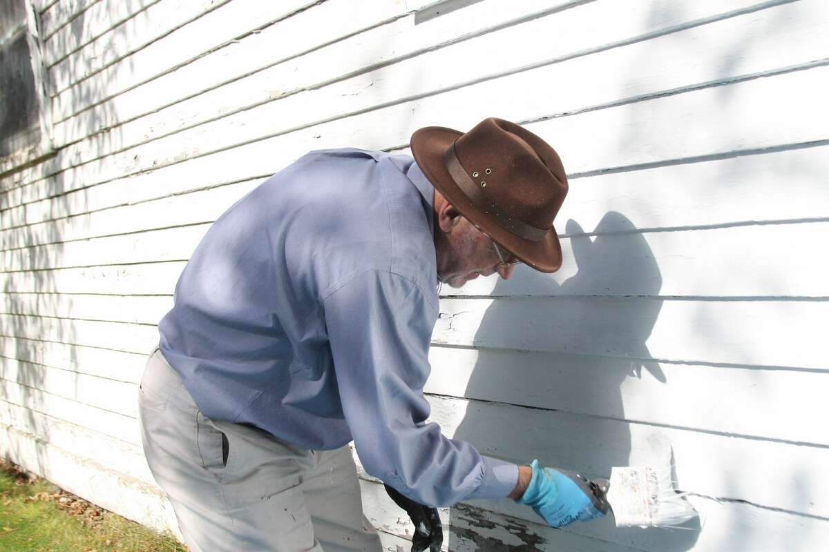 Ken Cooper puts a fresh coat of paint on Our Saviour's Historical Society in October of 2017. (News Advocate file photo)