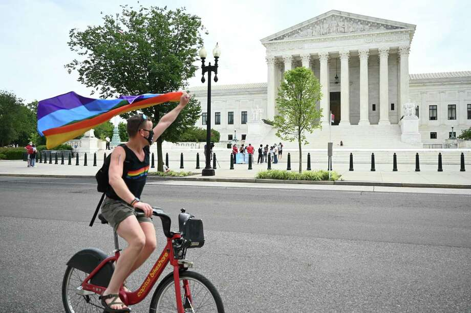 A man waves a rainbow flag as he rides by the US Supreme Court that released a decision Monday that says federal law protects LGBTQ workers from discrimination. Photo: JIM WATSON / AFP Via Getty Images / AFP or licensors
