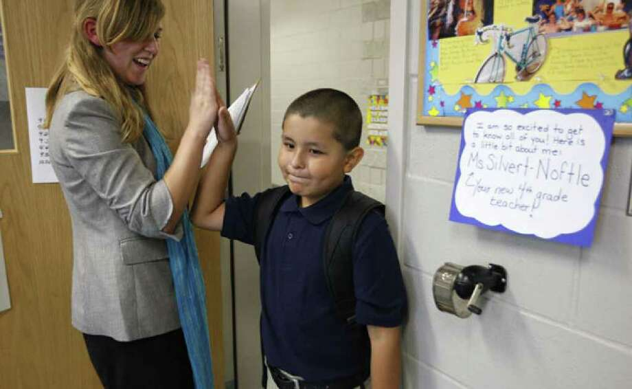 Teach for America teacher Erin Silvert-Noftle high-fives Julio Hernandez-Gonzalez on Monday, the first day of class at Crockett Elementary School. Silvert-Noftle is one of about 100 local members of the Teach for America program.