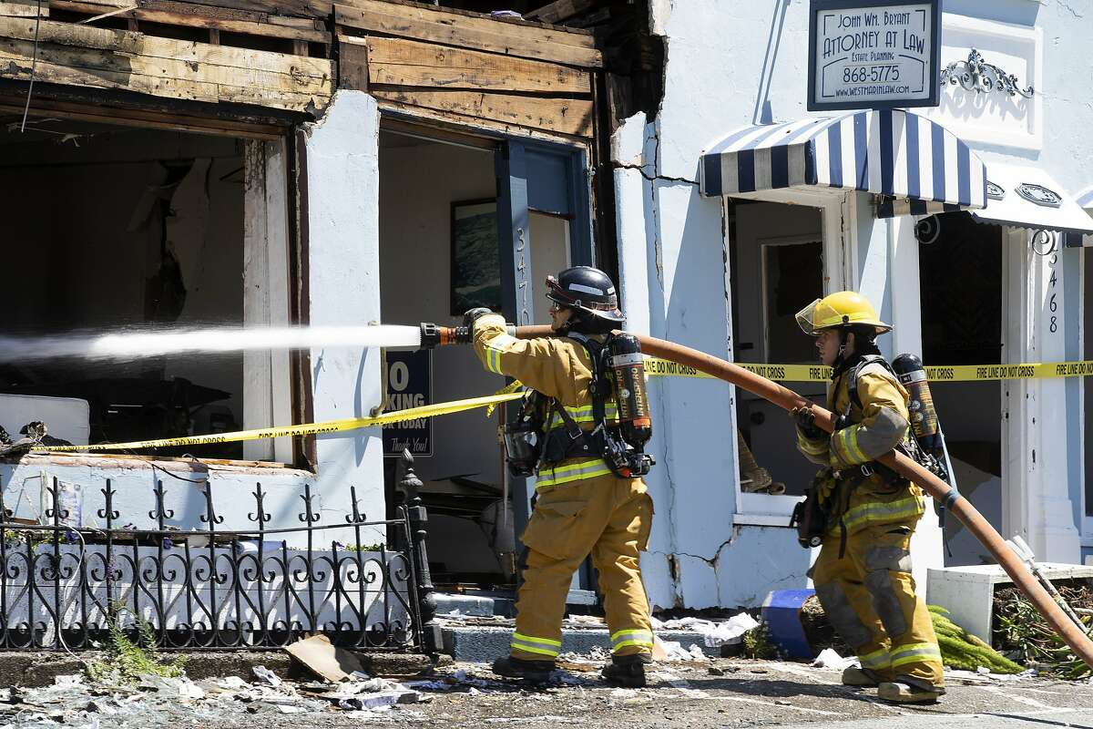 Firefighters pour water at the Oceanic Realty building at the site of an explosion along Shoreline Highway on Tuesday, June 16, 2020, in Stinson Beach, Calif.