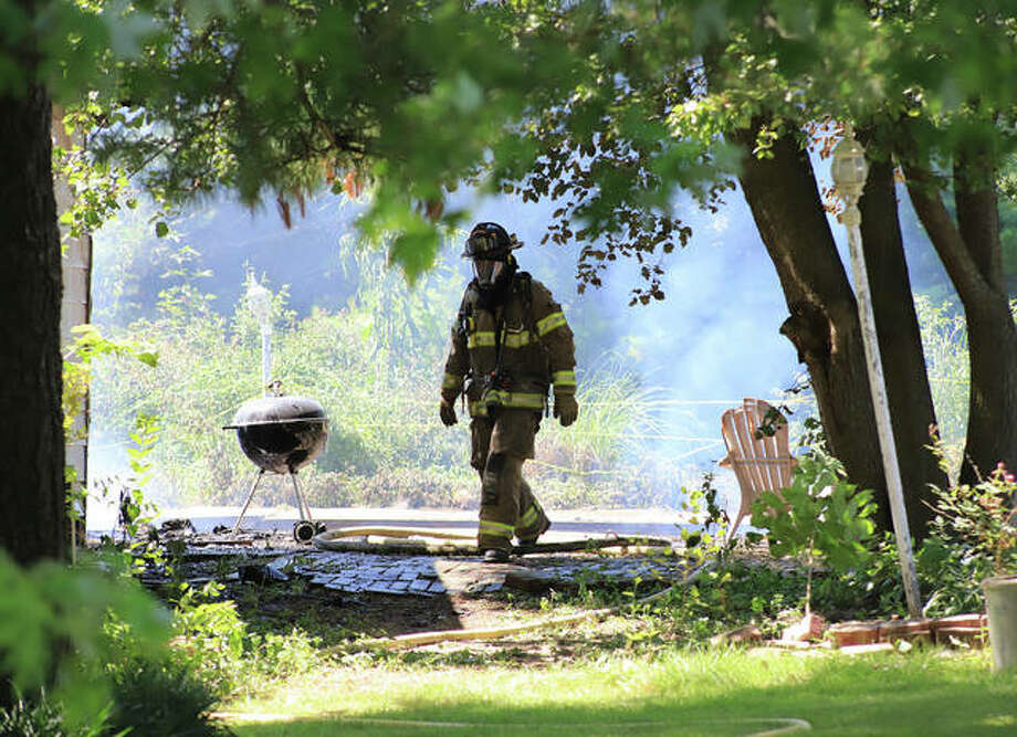 An Edwardsville firefighter walks through a property in the 3400 block of Glennoak Drive in rural Edwardsville. Officials Tuesday identified the victim as John L. Munsterman, 74, of Jerseyville. The house belonged to his son.