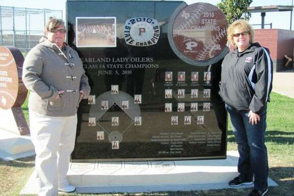 Pearland head softball coach Laneigh Clark, right, and associate head coach Michele Hydenpose alongside a monument dedicated to the Oiler's 2010 state championship softball team.