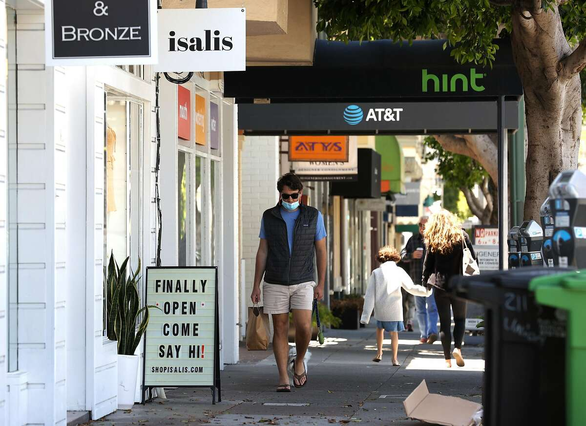 SAN FRANCISCO, CALIFORNIA - JUNE 16: A pedestrian walks by a retail store that has reopened on June 16, 2020 in San Francisco, California. According to a report by the U.S. Commerce Department, retail sales surged 17.7 percent in May as more states begin the process of reopening after being shut down due to the coronavirus COVID-19 pandemic. (Photo by Justin Sullivan/Getty Images)
