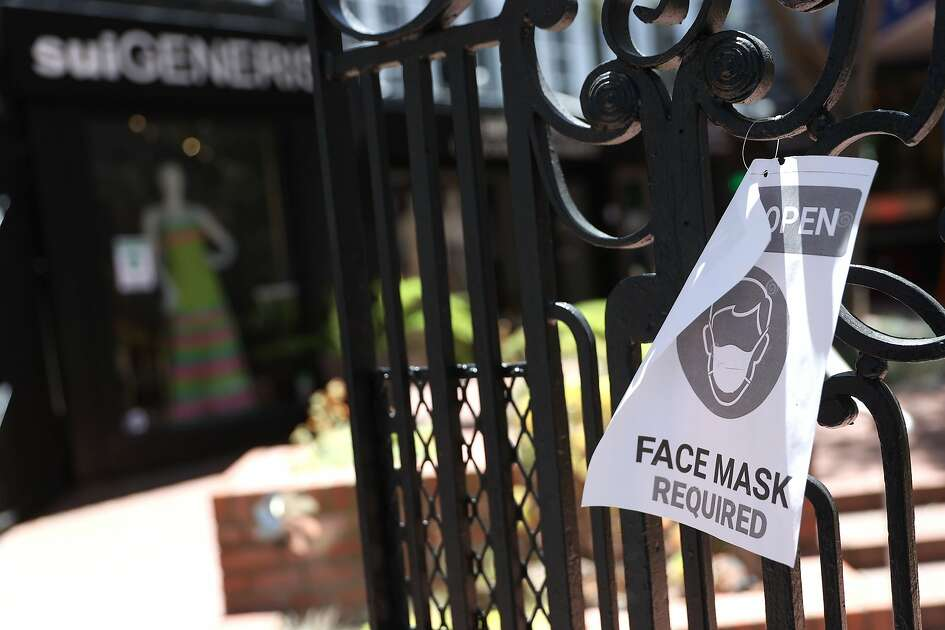 SAN FRANCISCO, CALIFORNIA - JUNE 16: A sign alerting customers to wear a mask is posted in front of a retail store that has reopened on June 16, 2020 in San Francisco, California. According to a report by the U.S. Commerce Department, retail sales surged 17.7 percent in May as more states begin the process of reopening after being shut down due to the coronavirus COVID-19 pandemic. (Photo by Justin Sullivan/Getty Images)