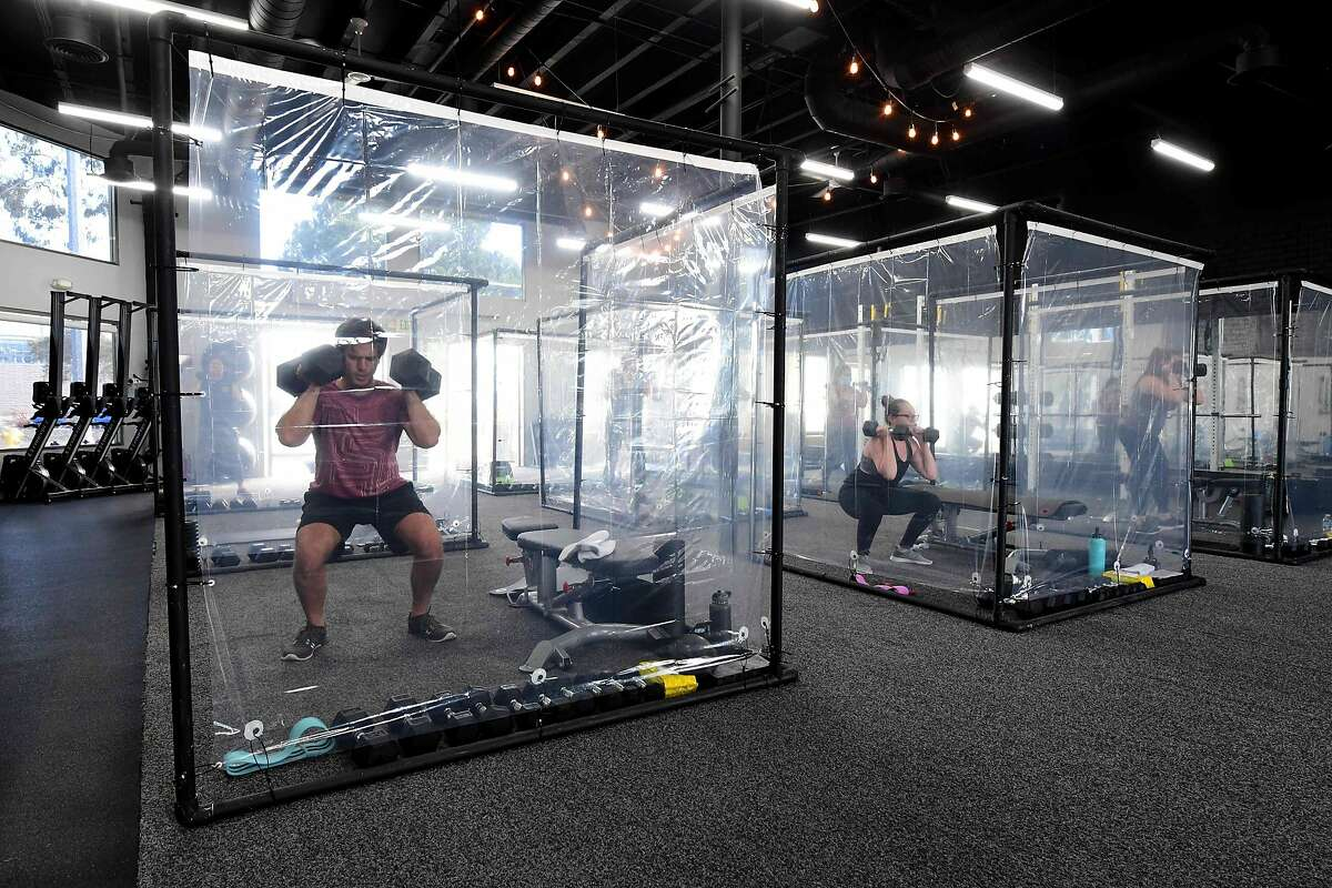 TOPSHOT - People exercise at Inspire South Bay Fitness behind plastic sheets in their workout pods while observing social distancing on June 15, 2020 in Redondo Beach, California, as the gym reopens today under California's coronavirus Phase 3 reopening guidelines. (Photo by FREDERIC J. BROWN / AFP) (Photo by FREDERIC J. BROWN/AFP via Getty Images)