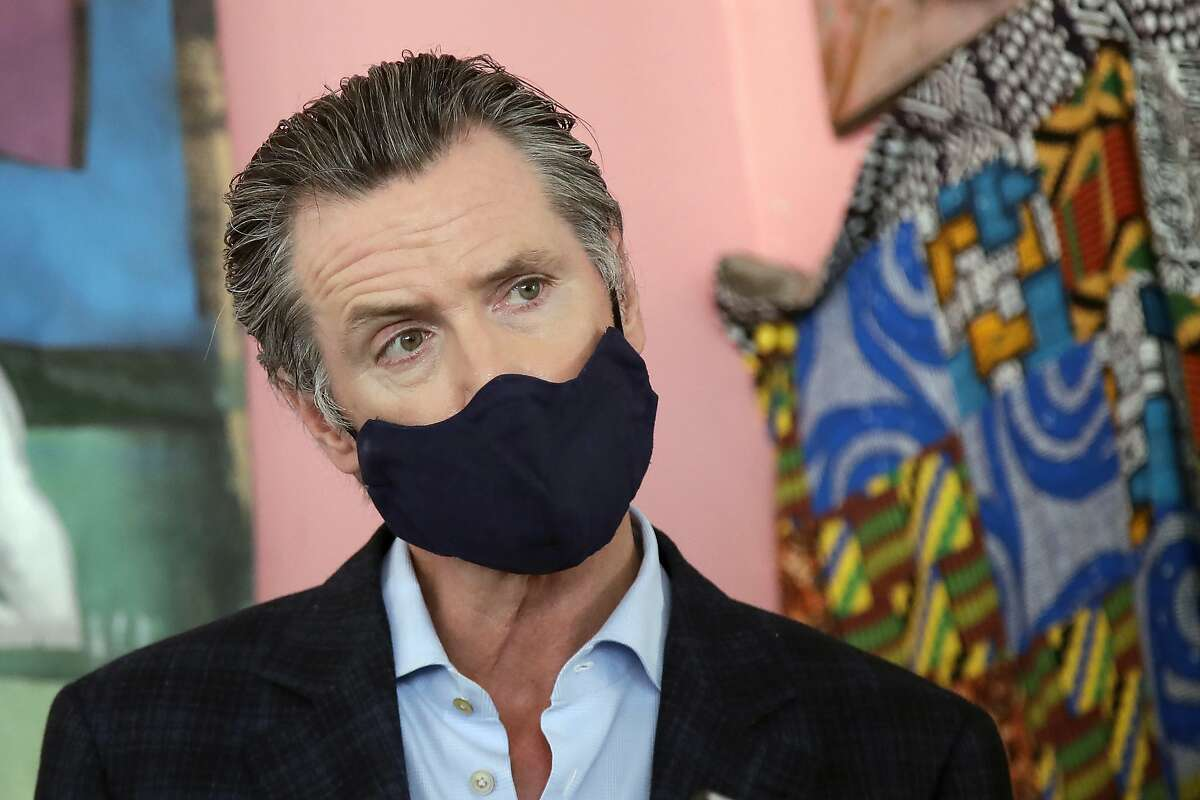 In this June 9, 2020, file photo, California Gov. Gavin Newsom wears a protective mask on his face while speaking to reporters at Miss Ollie's restaurant during the coronavirus outbreak in Oakland.