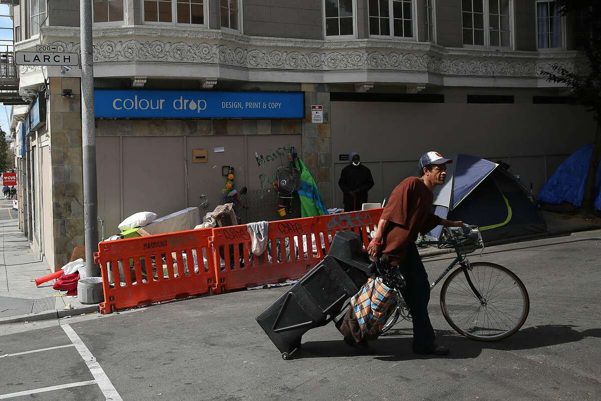 A man drags a bin as he walks a bicycle along Larch Street on Monday, June 15, 2020 in San Francisco, Calif.