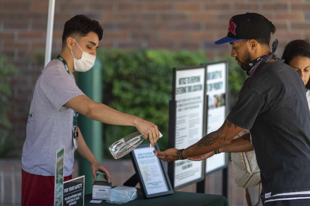 GLENDALE, CA - MAY 27: Masks and hand sanitizer are given to customers entering a Dick's Sporting Goods store as Los Angeles County retail businesses reopen while the COVID-19 pandemic continues on May 27, 2020 in Glendale, Californias latest guidelines and allow the resumption of in-store shopping at low-risk retail stores, faith-based services, drive-in theaters and other recreational activities with reduced capacities and social distancing restrictions, starting today. Not reopening yet are personal services locations like hair salons and dining in at restaurants. (Photo by David McNew/Getty Images)