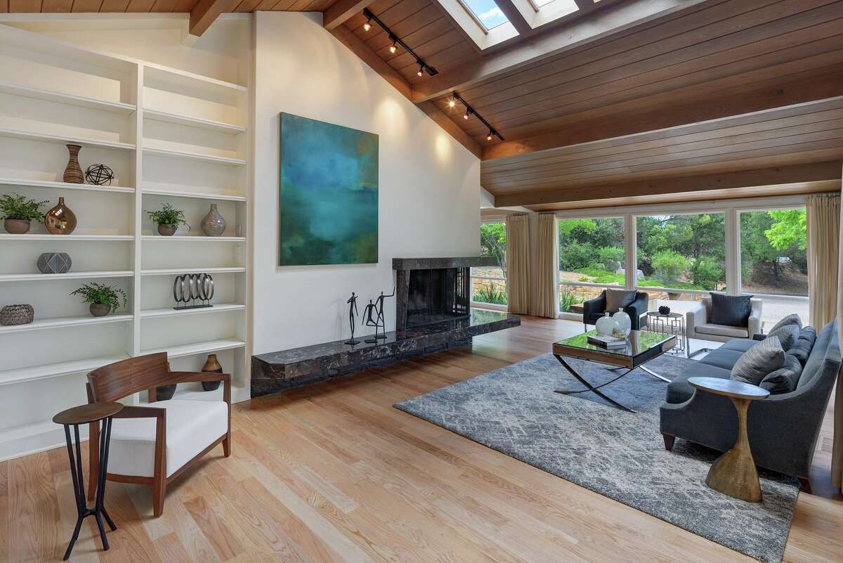 The interior features vaulted wood ceilings, hardwood floors, and floor-to-ceiling windows that bring the outdoors inside.