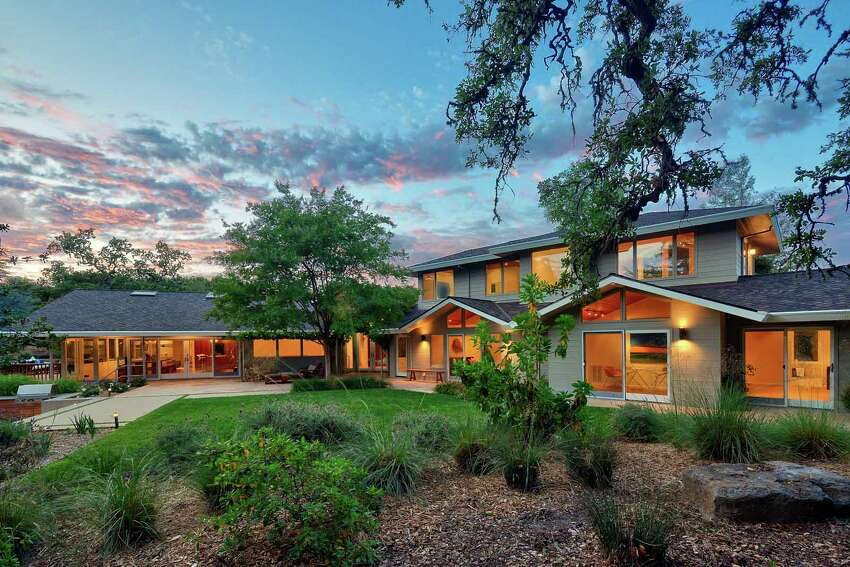 The home, at dusk, seems a tranquil alternative from all things city life. It even includes a mature olive tree grove, offering a shady spot on hot Portola Valley days.