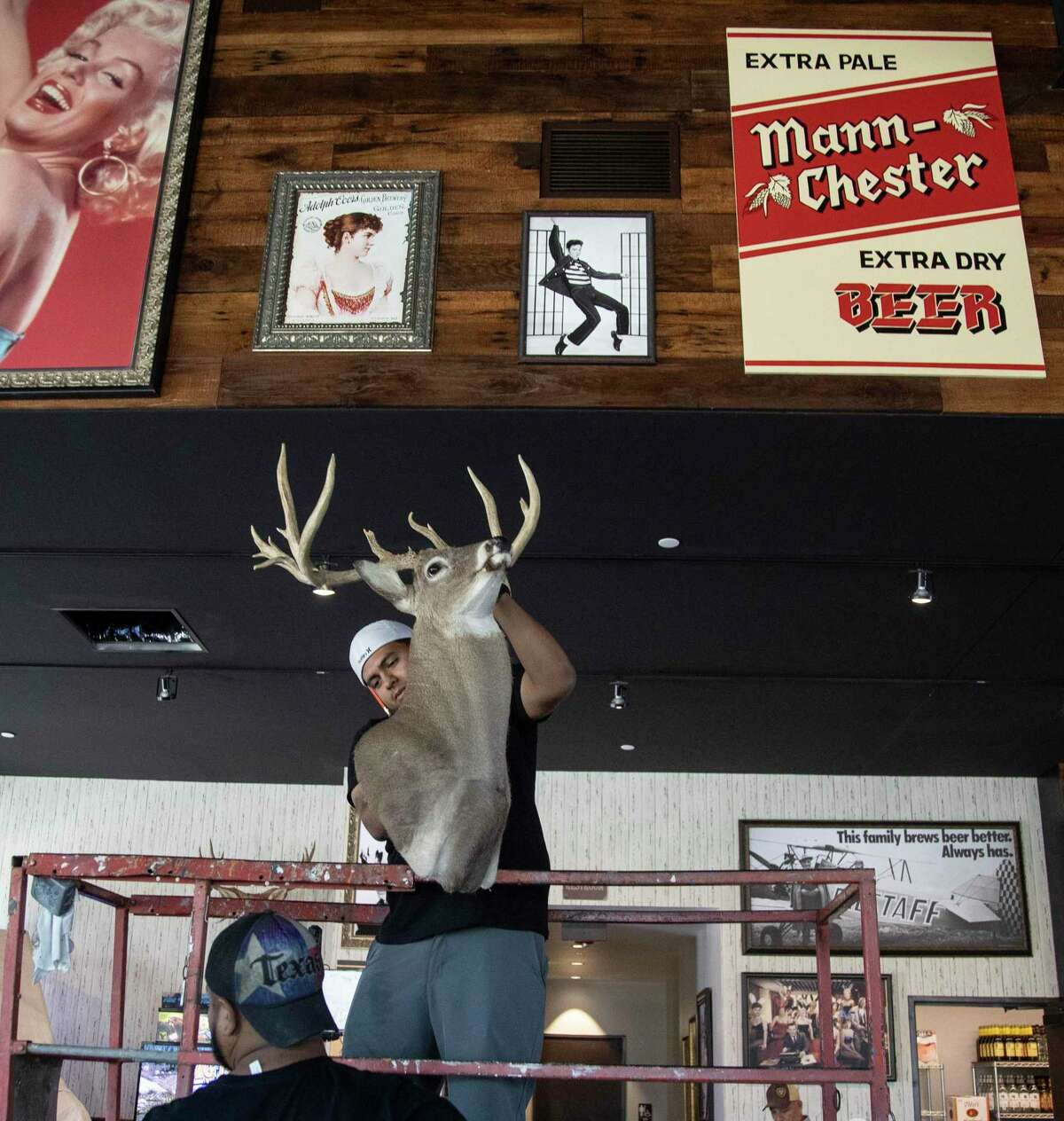 Leo Morales hangs a deer head on the wall at the a second location of Kirby Ice House, at 1015 Gessner Road, Friday, June 12, 2020, in Houston. The original Kirby Ice House is a bar in Upper Kirby known for its huge yard and laid back vibe. The second location is across the Katy Freeway from Memorial City Mall.