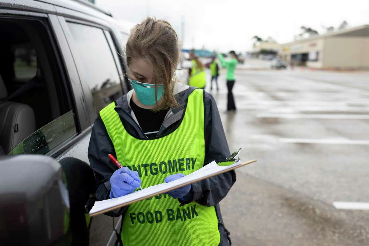 Taylor Penney takes the information of people needing food assistance at the Church Project in The Woodlands, Wednesday, April 29, 2020. Each family that was given a package received up to 100 pounds of food.