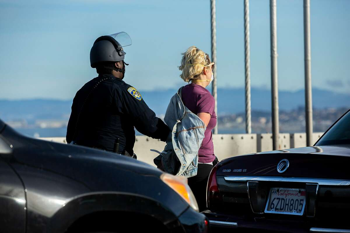 California Highway Patrol detain a person on the Bay Bridge, Sunday, June 14, 2020, in San Francisco, Calif. Approximately 50 vehicles rolled to a stop shortly after 4:30 p.m. on the upper deck in between Treasure Island and San Francisco, according to CHP officer Mark Andrews. They got out of their vehicles and spray painted BLM, for Black Lives Matter, on the deck of the bridge. Andrews said other writing is on the walls on the sides of the lanes. At least 27 protesters were arrested, according to San Francisco Sheriff's Office spokeswoman Nancy Crowley.