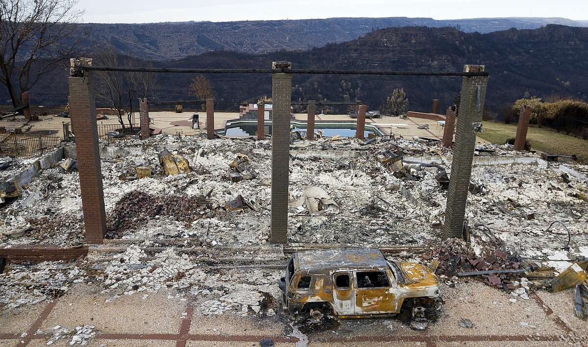 In this Dec. 3, 2018, file photo, a vehicle rests in front of a home leveled by the Camp Fire in Paradise, Calif.