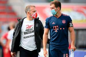 """Bayern Munich's German head coach Hans-Dieter Flick (L) wears a Tshirt with a message reading """"Red against racism 'Blacklivesmatter'"""" in solidarity with protests raging across the US over the death of George Floyd as he walks with Bayern Munich's German midfielder Leon Goretzka after the German first division Bundesliga football match Bayer 04 Leverkusen v FC Bayern Munich on June 6, 2020 in Leverkusen, western Germany. - The death during the arrest of George Floyd, an unarmed black man in the US state of Minnesota, has brought tens of thousands out onto the streets during a pandemic that is ebbing in Asia and Europe, but spreading in other parts of the world. (Photo by Matthias Hangst / POOL / AFP) / DFL REGULATIONS PROHIBIT ANY USE OF PHOTOGRAPHS AS IMAGE SEQUENCES AND/OR QUASI-VIDEO (Photo by MATTHIAS HANGST/POOL/AFP via Getty Images)"""