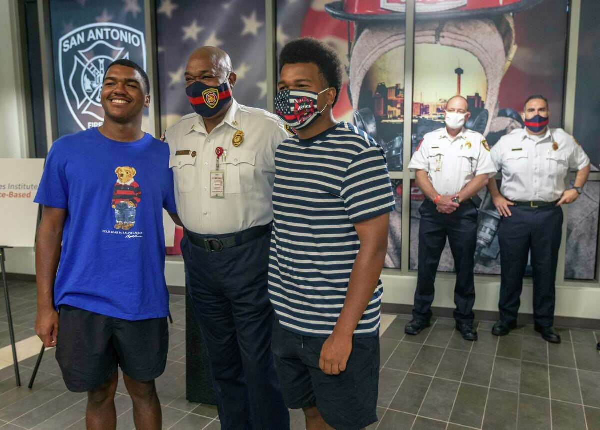 San Antonio Fire Department chief Charles Hood, center, poses for pictures with two of his sons, Langston, 19, left, and Sheridan, 17, after accepting the Metro Fire Chiefs Association's Fire Chief of the Year award at the San Antonio Public Safety Headquarters. While accepting the award Hood spoke about the Black Lives Matter movement, challenges he faced as San Antonio's first black fire chief, his personal experiences with racism during his life, and how he talks to his sons about being black in America.