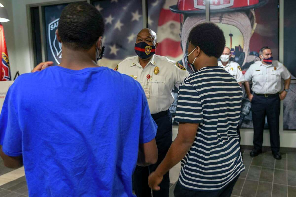 San Antonio Fire Department chief Charles Hood, center, talks with two of his sons, Langston, 19, left, and Sheridan, 17, after accepting the Metro Fire Chiefs Association's Fire Chief of the Year award at the San Antonio Public Safety Headquarters. While accepting the award Hood spoke about the Black Lives Matter movement, challenges he faced as San Antonio's first black fire chief, his personal experiences with racism during his life, and how he talks to his sons about being black in America.