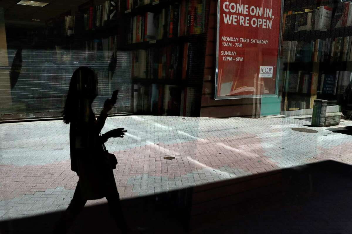 A passer-by holding a mobile device walks past a store window, Tuesday, June 16, 2020, in Cambridge, Mass. According to the Commerce Department U.S. retail sales jumped by a record 17.7% from April to May, with spending partially rebounding after the coronavirus had shut down businesses, flattened the economy and paralyzed consumers during the previous two months. (AP Photo/Steven Senne)