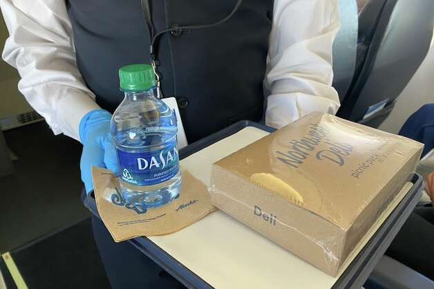 After a few minutes at cruising altitude, the flight attendant distributed a small bottle of Dasani water and a pre-packaged, airtight snack box, sealed with a film that is very difficult to peel off and no pull tabs to assist. Once I got it off I found nuts, chips, cheese spread, salami, some crackers and an Almond Roca inside. Photo: Chris McGinnis
