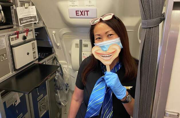 """On my return trip, which was more or less the same experience, our flight attendant had a new tool to express her happiness and hospitality — a smile on a stick — and it worked! Her """"smile"""" and overall attitude broke the ice with passengers and made a clinical-feeling flight a lot more fun. Kudos to her. Photo: Chris McGinnis"""
