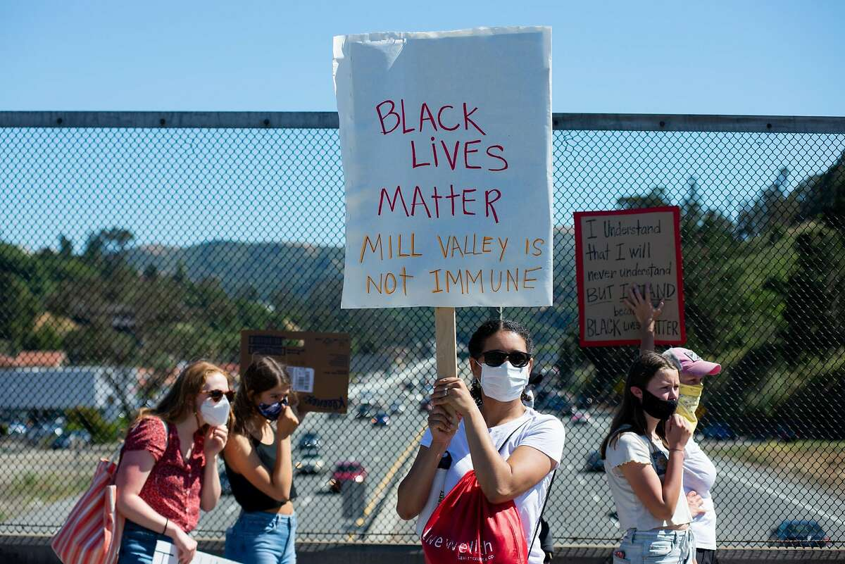 Demonstrators hold signs for cars to see on a highway overpass during a protest organized by a group of young people to support Black Lives Matter on June 16, 2020 in Mill Valley, Calif.