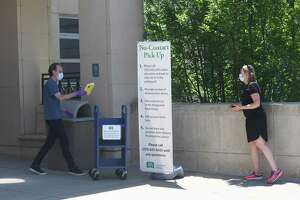 Library Technical Assistant Everett Perdue places a book on a cart for Cos Cob's Kathy Myer as part of the new no-contact pick up process at Greenwich Library in on Tuesday. The library began the first step of returning to in-person services by offering no-contact pick up for library books and materials.