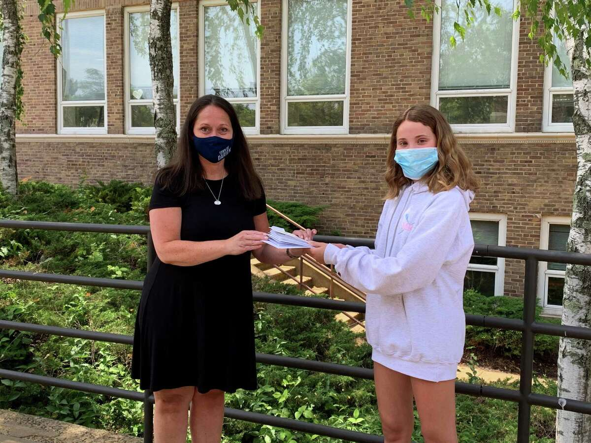 From left, Ali Ramsteck, director of Darien Human Services, is receiving donations of free gift certificates that have been donated through Rescue Main Street Darien, a gift card swap created by teen Sophie Curtis, right.