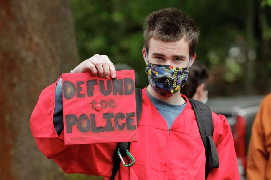 "Elliot Armitage, a 2020 graduate of Ballard High School, holds his mortarboard cap that reads ""Defund the Police"" as he prepares to take part in a cap and gown Black Lives Matter march with other high school graduates, Monday, June 15, 2020, in Seattle. The theme of the march as ""Walking for Those Who Can't,"" and organizers were calling for police funding reforms and an end to Seattle public schools' relationship with the Seattle Police Department. (AP Photo/Ted S. Warren) / Copyright 2020 The Associated Press. All rights reserved."