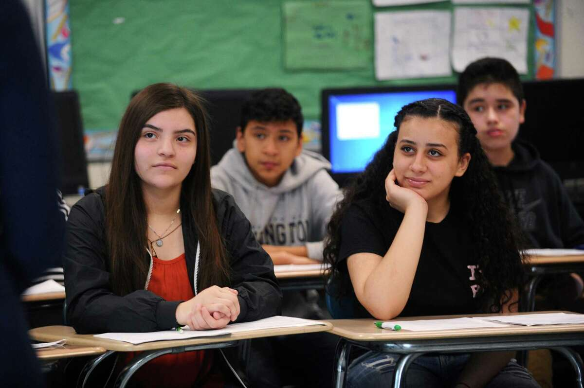 Eighth graders Amairany Medina, left, and Sofia Elkababi listen to Rep. Caroline Simmons, D- Stamford, speak at Turn of River Middle School in Stamford, Conn. on Monday, March 26, 2018. The students are part of the AVID program, which stands for advancement via individual determination.