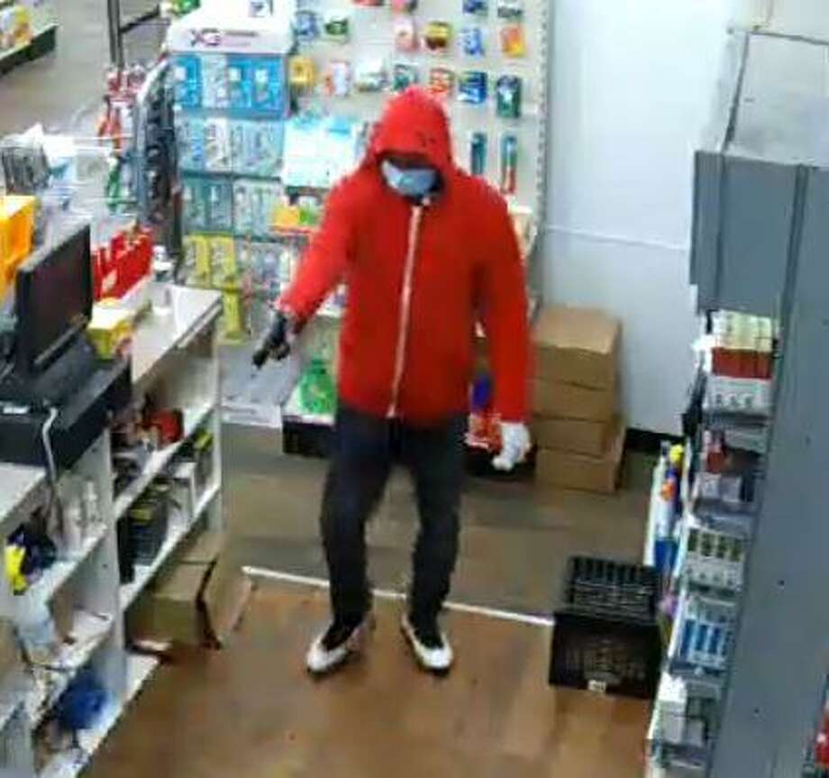 A man uses a handgun to rob the Mobil gas station and convenience store at 904 West Main Street on Tuesday, June 16, 2020. On the same evening, a man wearing the same clothes robbed the West Main Street Grocery — which has been held up three times this year. Photo: Stamford Police Department / Contributed