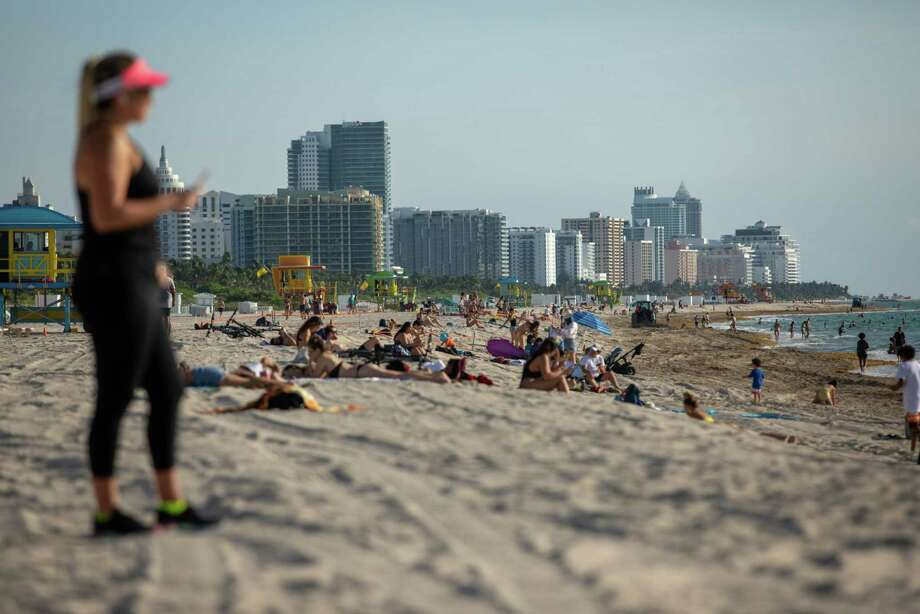 People sit on the beach in Miami Beach on June 10. 2020. Photo: Bloomberg Photo By Jayme Gershen. / © 2020 Bloomberg Finance LP