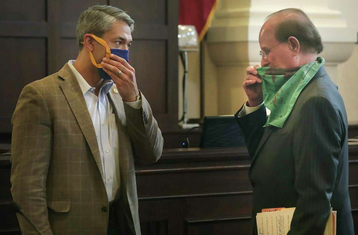 Bexar County Judge Nelson Wolff, right, and Mayor Ron Nirenberg, adjust their masks following a press conference to announce a new executive order to help fight the resurgence of novel coronavirus, at the Bexar County Courthouse, on Wednesday, June, 17, 2020.