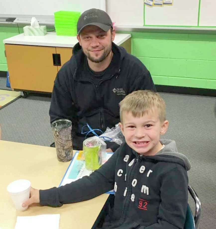 Dusty Maurer is pictured with his youngest son, Nate, at Bad Axe Elementary's Donuts with Dad event in 2019. (Robert Creenan/File Photo)