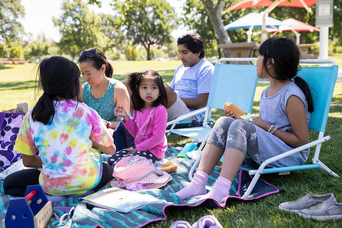 Oahn Mendal (left) and Sanjit Mendal (center) spend time with their children while having a picnic at Heather Farm Park in Walnut Creek, Calif. Tuesday, June 9, 2020. They Bay Area is opening at a fairly fast pace, with Contra Costa County announcing plans this week to reopen indoor dining and hair salons soon, while it reports near-record new cases.