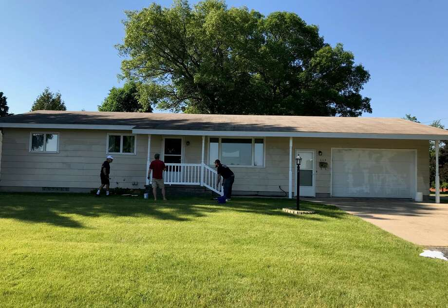 Sheila Bajtka shared this photo of several volunteers painting her father's home in Manistee after it was spray painted with graffiti Sunday. Photo: Sheila Bajtka/Courtesy Photo