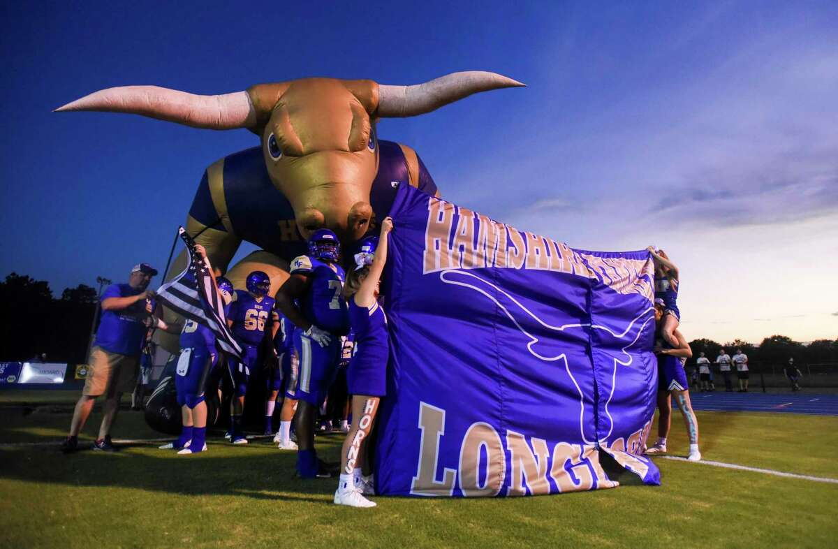 Hamshire-Fannett cheerleads hold a banner in front of the football players for them to run through before the game against Tarkington at Longhorn Stadium in Hamshire Friday night. Photo taken on Friday, 09/27/19. Ryan Welch/The Enterprise