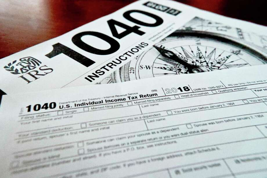 FILE- This Feb. 13, 2019, file photo shows multiple forms printed from the Internal Revenue Service web page that are used for 2018 U.S. federal tax returns in Zelienople, Pa. IRS data released Thursday, April 25, shows that while the average refund fell, the tax filing season was largely unchanged by the massive tax overhaul. (AP Photo/Keith Srakocic, File) Photo: Keith Srakocic, STF / Associated Press / Copyright 2019 The Associated Press. All rights reserved