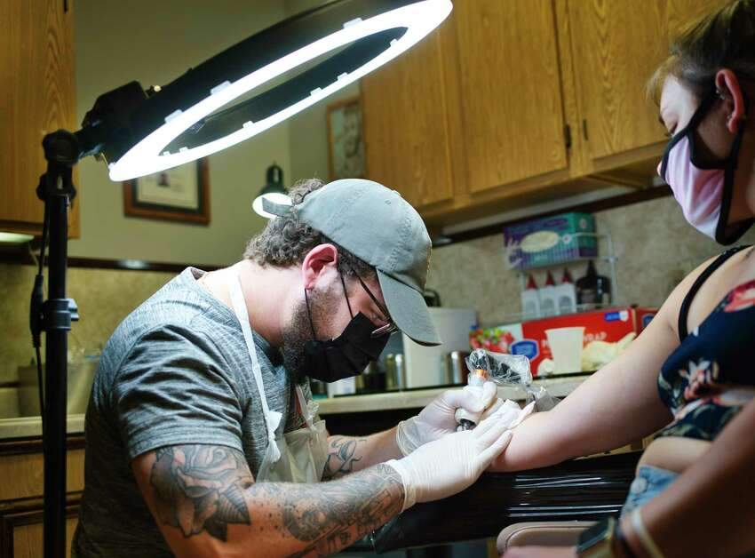 Tattoo artist Elija Ortiz inks medical alert symbol on the wrist of Sadie Dunne of Albany at Tom Spaulding Tattoo and Body Piercing Studio on Wednesday, June 17, 2020, in Albany, N.Y. Wednesday was the first day that tattoo shops could reopen for business. (Paul Buckowski/Times Union)