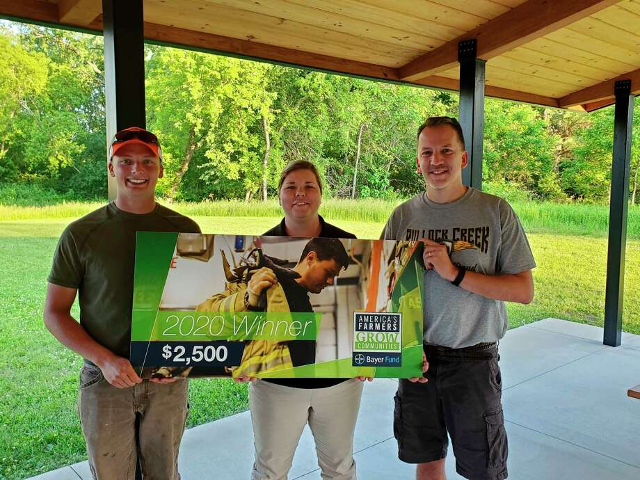 From left, Ryan Garrett of Garrett Farms; Josephine Bossenberger, band director and Joel Beeck, Band Booster president celebrate the acceptance of the $2,500. (Photo provided)