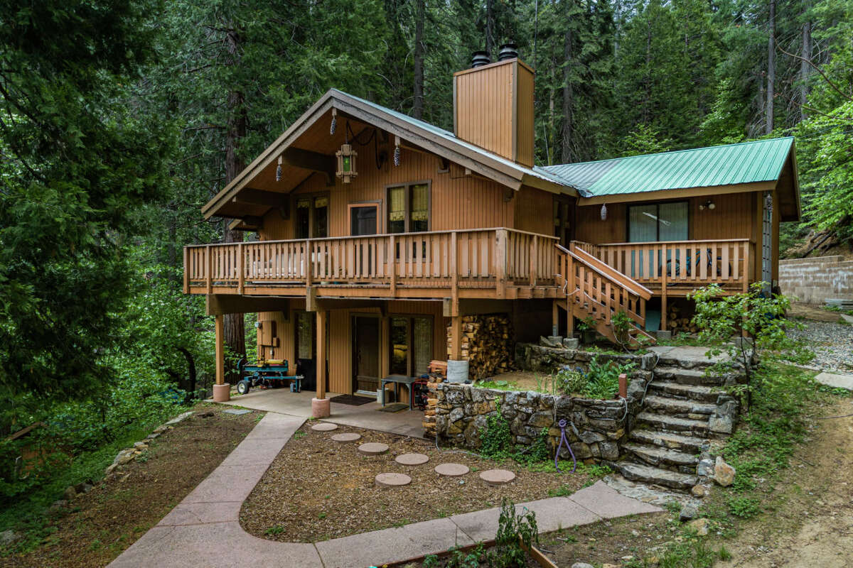 Built in 1973, the wooden house boasts high beams and decks on front and back. The main house and downstairs apartment can be occupied separately with separate entrances. The sprawling land that sits largely outside the boundaries of the park has areas identified as locations for further cabin builds, with astounding views amid the towering conifers and rocky Sierra outcrops.