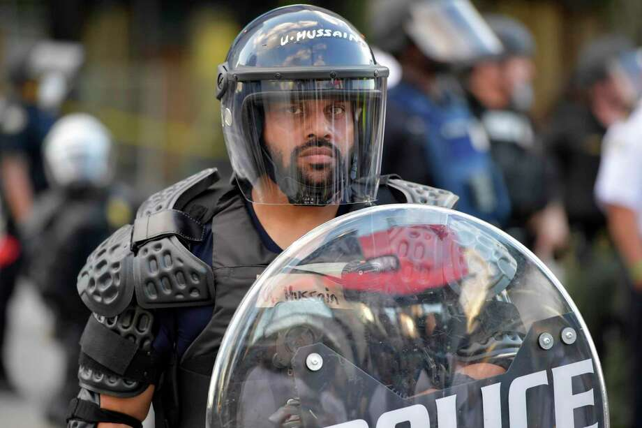 A policeman monitors demonstrators protesting recently in Atlanta. on Saturday in Atlanta. American policing is going to emerge changed from the June protests, but how it changes remains unclear. Photo: Mike Stewart /Associated Press / Copyright 2020 The Associated Press. All rights reserved