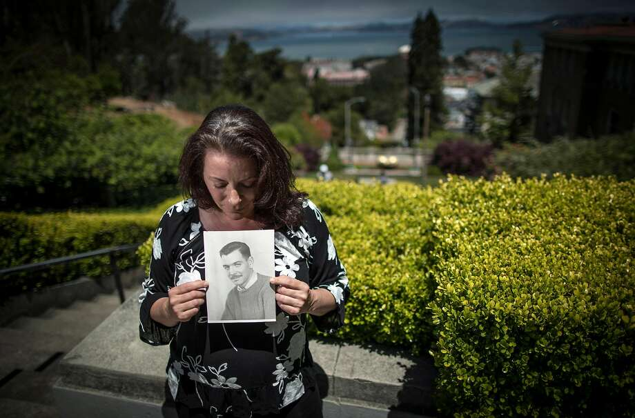 COVID-19 survivor Chloe Barr holds a photo of her late father at the Lyon Street steps near her home in San Francisco. Photo: Carlos Avila Gonzalez / The Chronicle