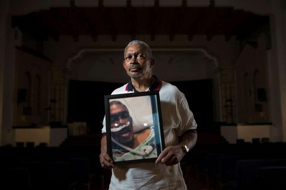 Pastor Johnnie Clark, Sr., the 72-year-old minister who coordinates the Love in Action hunger relief ministry at Word Assembly Church in Oakland, holds a picture of himself when he was hospitalized with COVID-19. Photo: Carlos Avila Gonzalez / The Chronicle